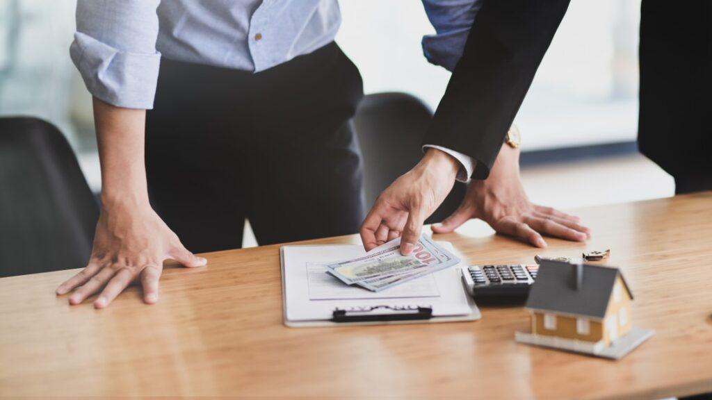 Contrato de locação de bem imóvel - duas pessoas perto de uma mesa com documentos, dinheiro, calculadora